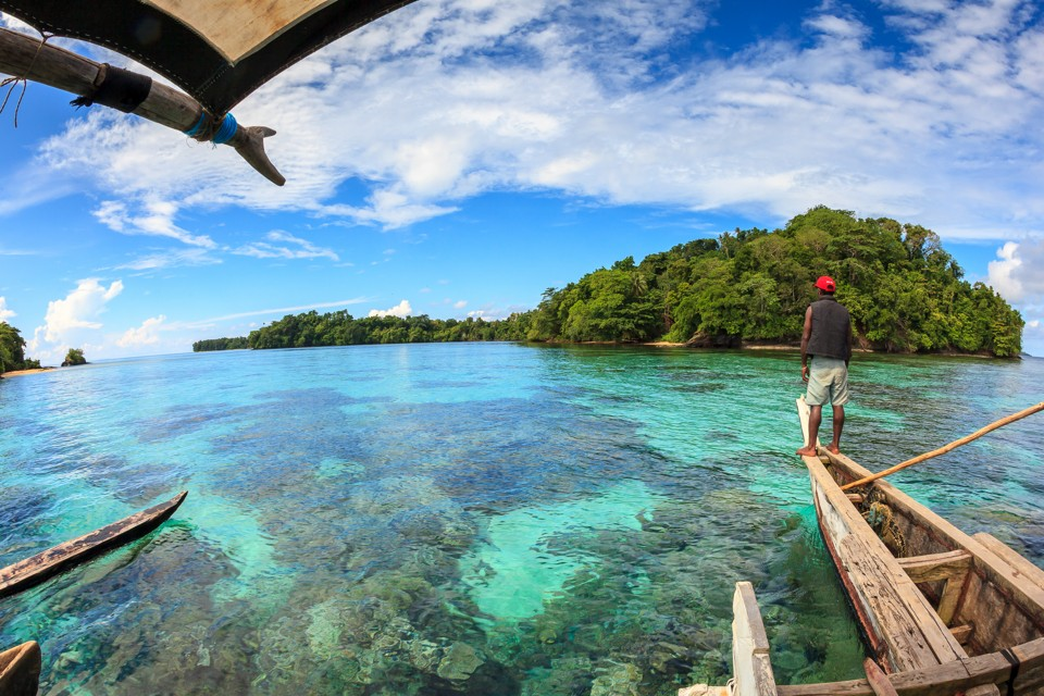 """A Titan villager navigates a traditional melanesian outrigger over shallow corals that flank a small island in the Manus Province of Papua New Guinea. Mystery shrouds the densely vegetated island, as legend amongst the indigenous Mbuke people maintains that it is home to a """"dinosaur"""" that has never been seen on any other island in the Archipeligo."""